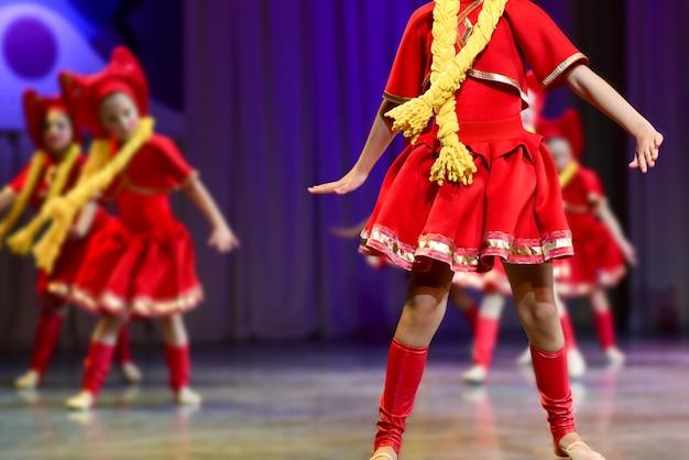 Młode dziewczyny w czerwonych sukienkach tańczą na scenie rosyjskie tańce ludowe