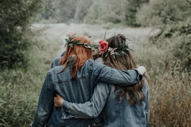 Młode dziewczyny w pięknych sukienkach i dżinsowych kurtkach w parku