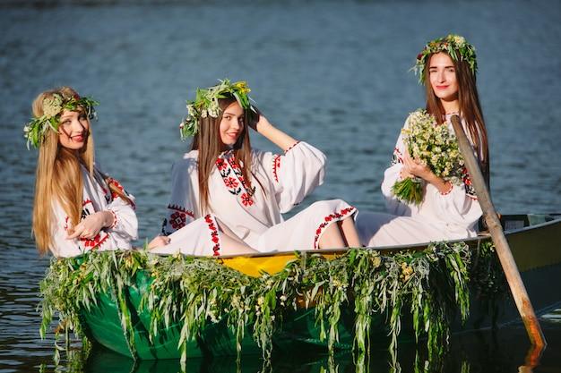 Młode dziewczyny w strojach ludowych pływają łodzią ozdobioną liśćmi i porostami. słowiańskie święto iwana kupały.
