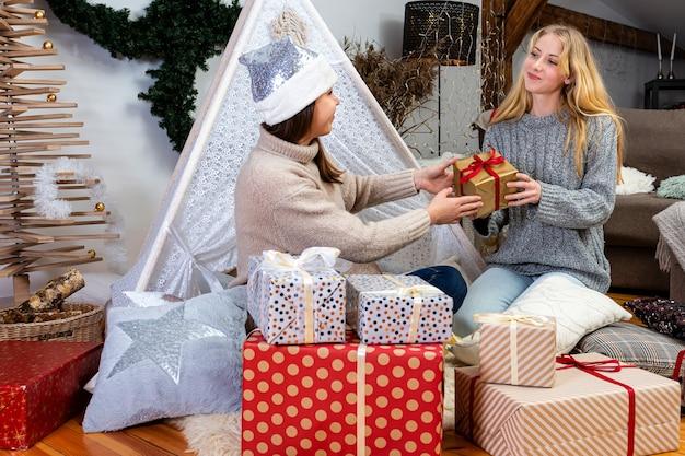 Młode dziewczyny zabawy, pakowanie prezentów w domu