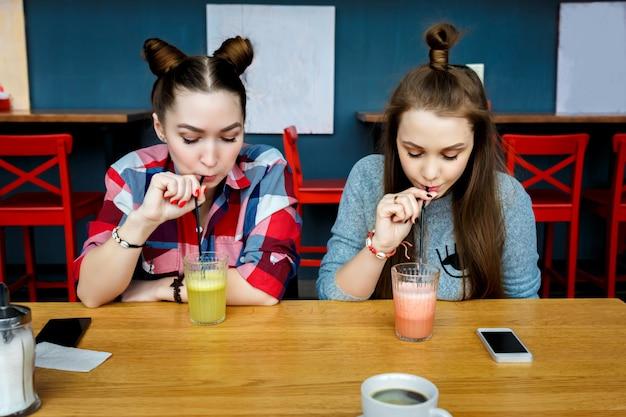 Młode dziewczyny zabawy w barze-kawiarni