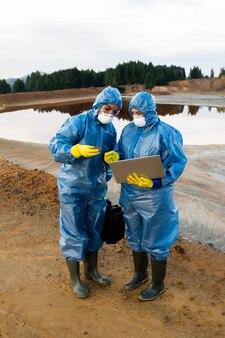 Młode ekologki w ochronnych ubraniach roboczych stoją na zanieczyszczonej glebie lub glinie na brudnej rzece i robią notatki w laptopie