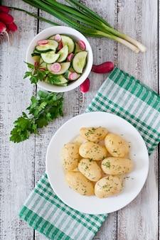 Młode gotowane ziemniaki z masłem i koperkiem na białym talerzu