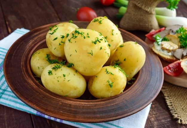 Młode gotowane ziemniaki z masłem i koperkiem w glinianej misce na drewnianym stole