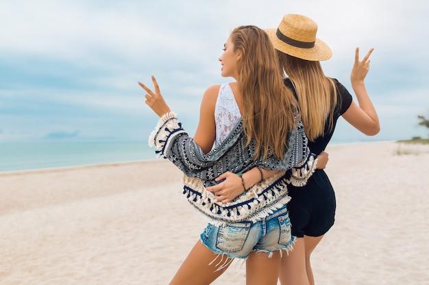 Młode hipster piękne kobiety na wakacjach na tropikalnej plaży, stylowy letni strój, szczęśliwy, trend w modzie, styl hippie, modne akcesoria, przyjaciele razem, pozytywny nastrój, widok z tyłu