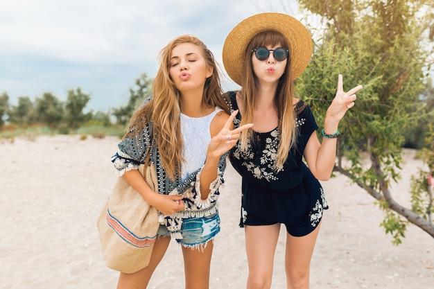 Młode hipster piękne kobiety na wakacjach na tropikalnej plaży, stylowy letni strój, uśmiechnięty szczęśliwy, trend w modzie, czarno-biały styl hippie, modne akcesoria, przyjaciółki bawiące się razem