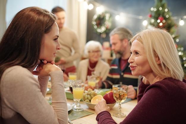 Młode i dojrzałe kobiety o czymś dyskutują przy uroczystym stole podczas rodzinnej kolacji w wigilię bożego narodzenia