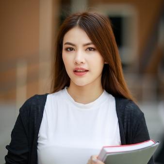Młode i piękne azjatyckie dziewczyny studentki trzymają książki, pozują do kamery przed budynkiem szkoły. nauka i przyjaźń koncepcji bliskiego przyjaciela nastolatków.