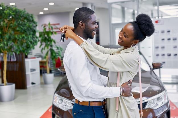 Młode i piękne małżeństwo w salonie samochodowym
