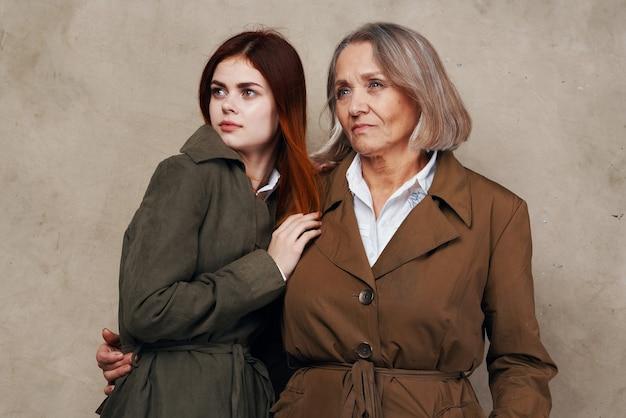 Młode i stare kobiety stoją obok siebie jesień studio mody na białym tle. zdjęcie wysokiej jakości