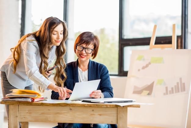 Młode i starsze kobiety biznesu pracujące razem nad dokumentami w nowoczesnym wnętrzu biurowym