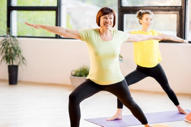 Młode i starsze kobiety uprawiające sport noszą wspólne ćwiczenia jogi w domu lub na siłowni