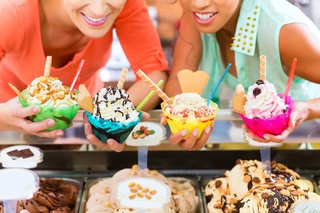 Młode klientki lub koleżanki z różnego rodzaju lodami na rożki, rożki i lody w salonie