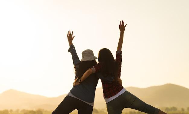 Młode kobiety bawią się razem z podniesionymi rękami przed górą podczas zachodu słońca szczęście sukces przyjaźń i koncepcje społeczności community