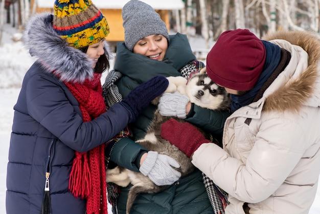 Młode kobiety bawiące się ze szczeniakiem