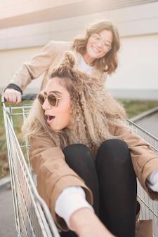 Młode kobiety bawić się z wózek na zakupy