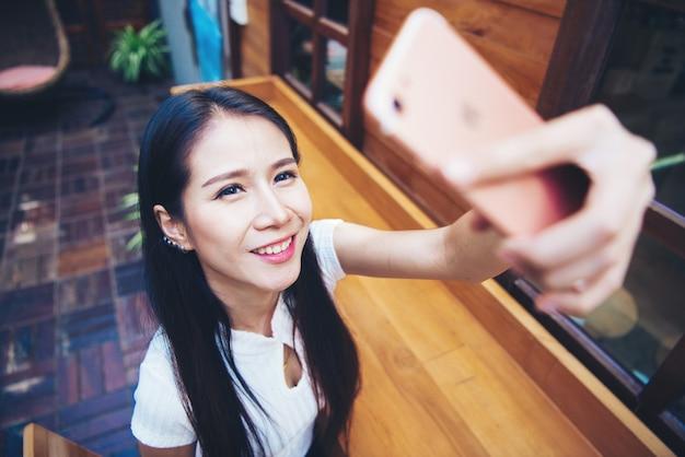Młode kobiety biorą selfie od ręki z mądrze telefonem