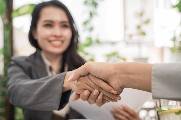 Młode kobiety biznesu uścisnąć dłoń w kawiarni
