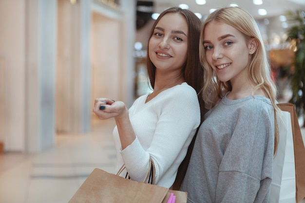 Młode kobiety cieszy się robić zakupy wpólnie przy centrum handlowym