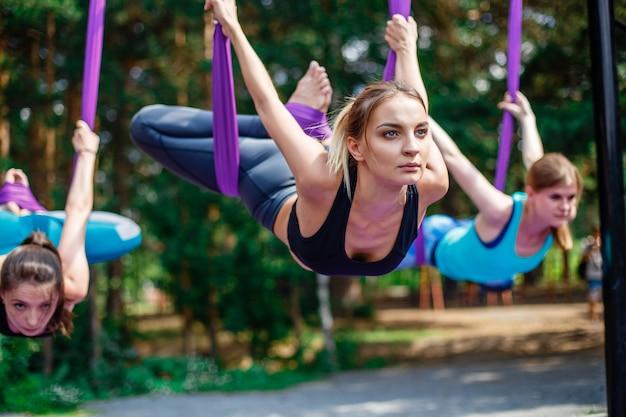 Młode kobiety, ćwiczenia jogi antygrawitacyjnej z grupą ludzi na zewnątrz.