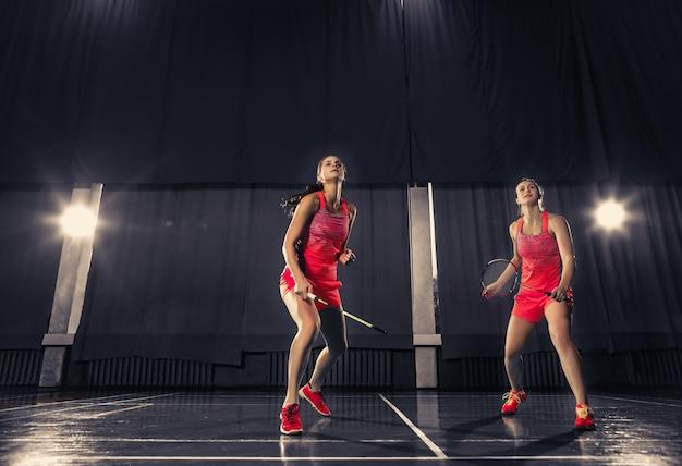 Młode kobiety, grając w badmintona na siłowni