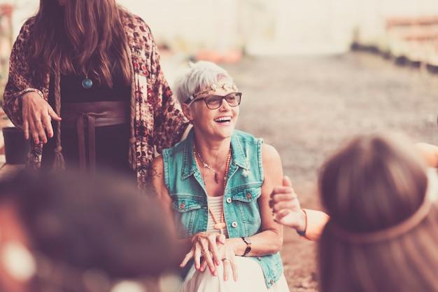 Młode kobiety i dziewczęta w przyjaźni razem świętują i bawią się w bio-naturalnym miejscu. uśmiechy i śmiech dla grupy hipisów alternatywna koncepcja stylu życia