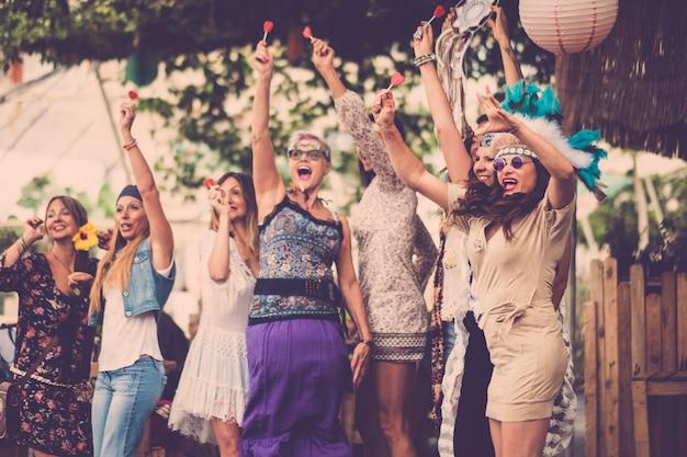 Młode kobiety i dziewczęta w przyjaźni wspólnie świętują i bawią się w ekologicznym miejscu. uśmiecha się i śmieje się dla grupy hipisów alternatywnych koncepcji stylu życia