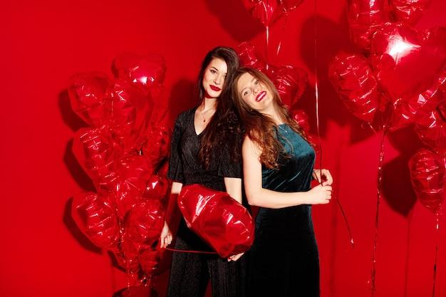 Młode kobiety imprezują z balonami w kształcie serca na walentynki