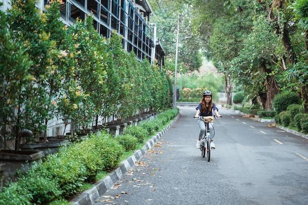 Młode kobiety jedzie składanie jechać na rowerze na drodze