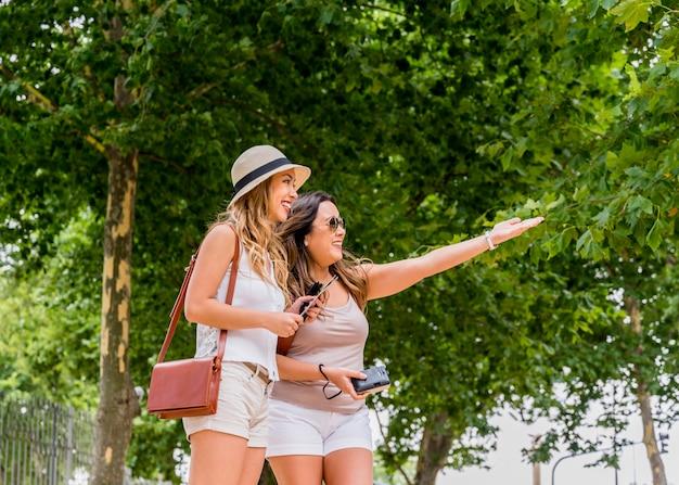 Młode kobiety jest ubranym kapelusz i niesie naramienną torbę patrzeje jej żeńskiego przyjaciela pokazuje coś