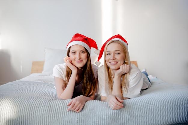 Młode kobiety jest ubranym santa ono uśmiecha się i kapelusz. dwie piękne dziewczyny leżące na łóżku. uśmiechnięte i czatujące dziewczyny. poziomy widok koncepcji przyjaźni i uroczystości.