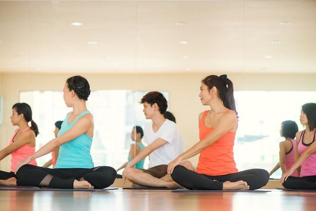 Młode kobiety jogi w pomieszczeniu zachowują spokój i medytują podczas uprawiania jogi do zbadania wewnętrznego pokoju. joga i medytacja mają dobre korzyści dla zdrowia. koncepcja fotografii dla jogi sport i zdrowego stylu życia