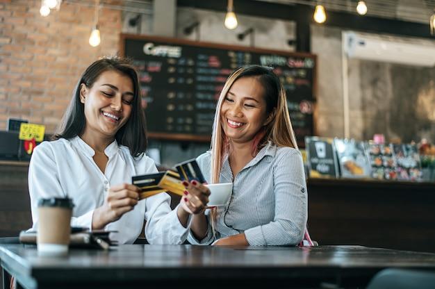 Młode kobiety lubią robić zakupy kartami kredytowymi.