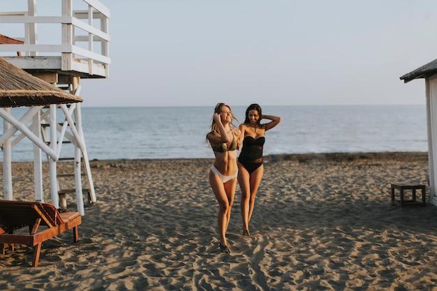 Młode kobiety ma zabawę przy wakacjami na plaży