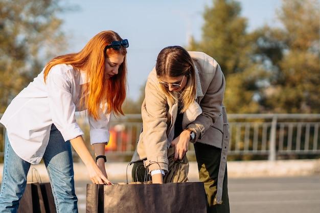 Młode kobiety moda z torby na zakupy na parkingu