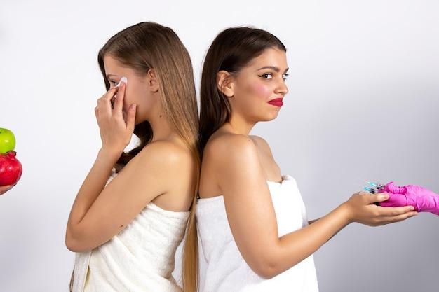 Młode kobiety na białej ścianie w wyborze między zabiegami kosmetycznymi a zdrową pielęgnacją