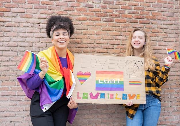 Młode kobiety na ulicy, ciesząc się, trzymając flagę dumy gejowskiej podczas protestu.