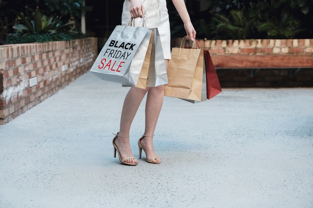 Młode kobiety niesie torba na zakupy, czarny piątek sprzedaży pojęcie