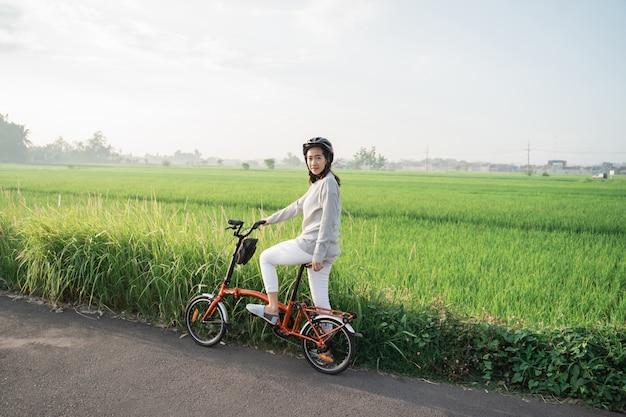 Młode kobiety noszą kaski do jazdy na składanych rowerach na polach ryżowych