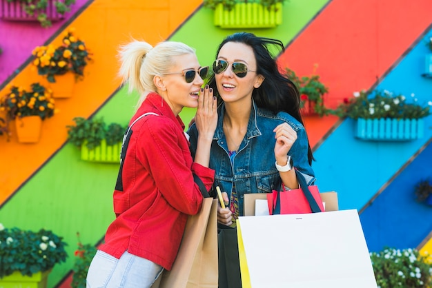 Młode kobiety opowiada blisko ściany z torbami