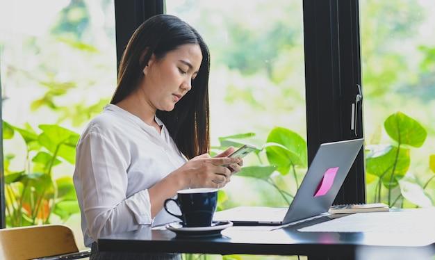 Młode kobiety patrząc na smartfona, rób zakupy online.