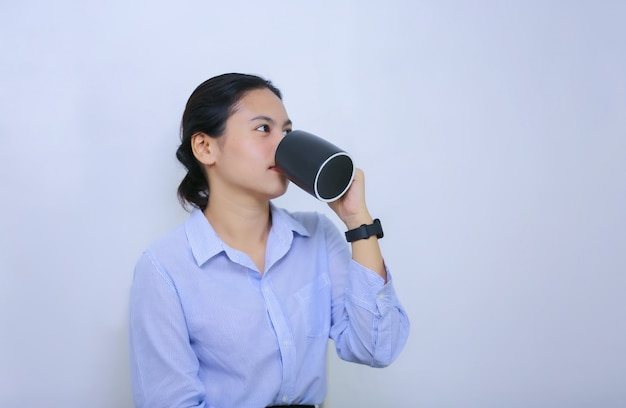 Młode kobiety pije kawę przeciw białemu tłu