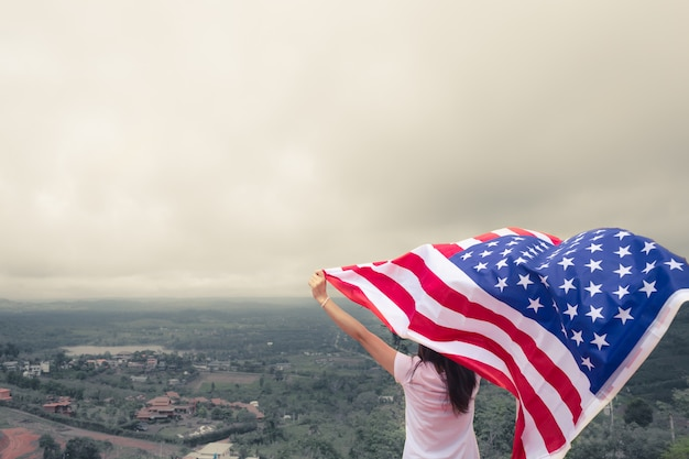 Młode kobiety podnoszą flaga amerykańską przeciw niebieskiemu niebu. dzień niepodległości, 4 lipca