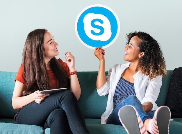 Młode kobiety pokazujące ikonę skype