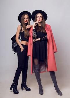 Młode kobiety pozują i noszą stylowe czarne kapelusze