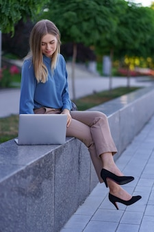Młode kobiety pracują na laptopie na placu miasta