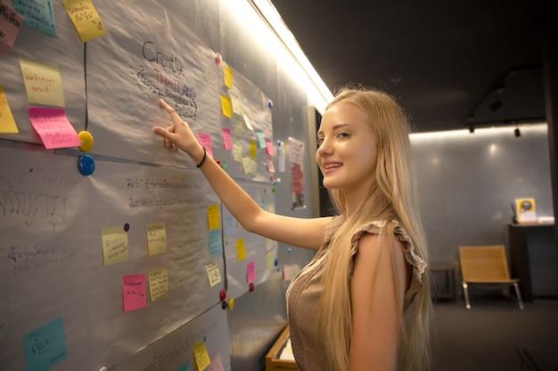 Młode kobiety przyklejają posty na tablicy pomysłów burza mózgów i organizowanie tablicy na tablicy