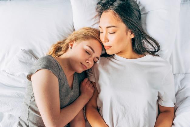 Młode kobiety przytulane śpiące w łóżku