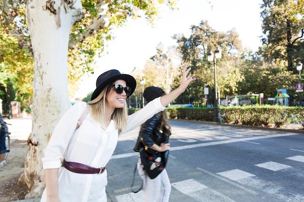 Młode kobiety przywołujące taksówkę