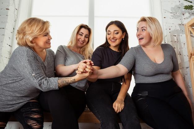 Młode kobiety rasy kaukaskiej w ubranie, wspólna zabawa. przyjaciele siedzą przy oknie i śmieją się, spędzają razem czas. pozytywne ciało, odżywianie, feminizm, kochanie siebie, koncepcja piękna.